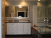 Master bathroom remodeling in Calabasas with custom white vanity, wall mount light fixture, frameless shower door, white frame mirror, Jacuzzi tum