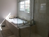 Inlay Jacuzzi with a shower separated by clear glass that is part of the frameless shower door