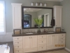 Custom double sink vanity with dark color fram mirror above the vanity, Caesar stone counter top, wall mount light fixture