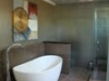 Free standing tub next to a pony wall cover with tile