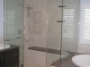 Custom shower remodeling with a bench, Caesar stone and frameless shower door