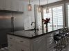 Modern kitchen remodeling with whits cabinets, dark color Granite counter top, an island with pendents lights above it