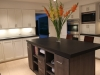 Kitchen island with dark color cabinets and Black caesar stone counter top